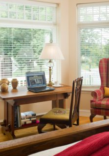A room shows a bed, a comfortable seating area, and a desk with window views.