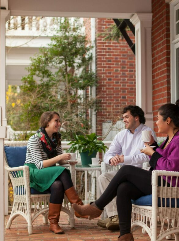 Three friends enjoying coffee on the front porch of the brick sided inn.