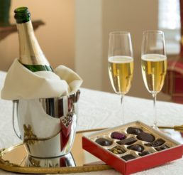 A bottle of campagne and two glasses rest next to a box of truffles