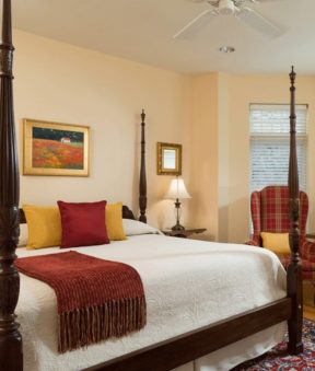 A room features large sunny windows, a four post king sized bed, and a comfortable seating area