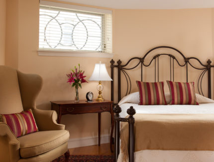 A room feautres a plush bed and sunny windows plus a comfortable chair and nightstand